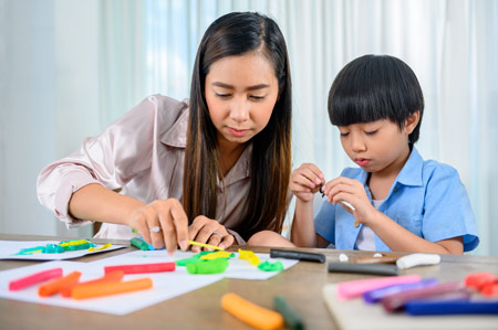 asian woman and boy working together with craft and writing supplies