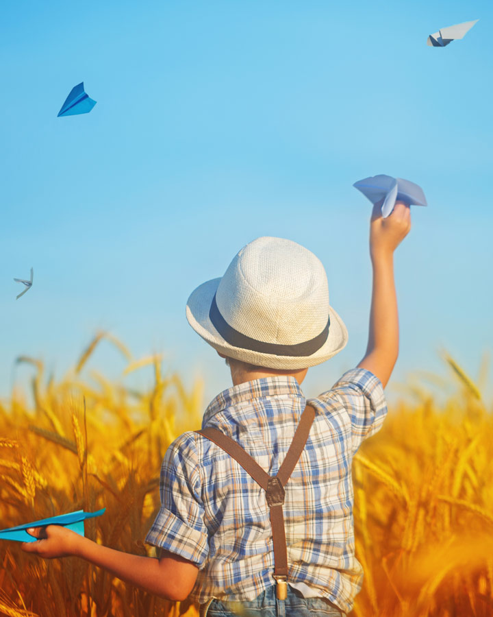 kid in field holding paper airplane